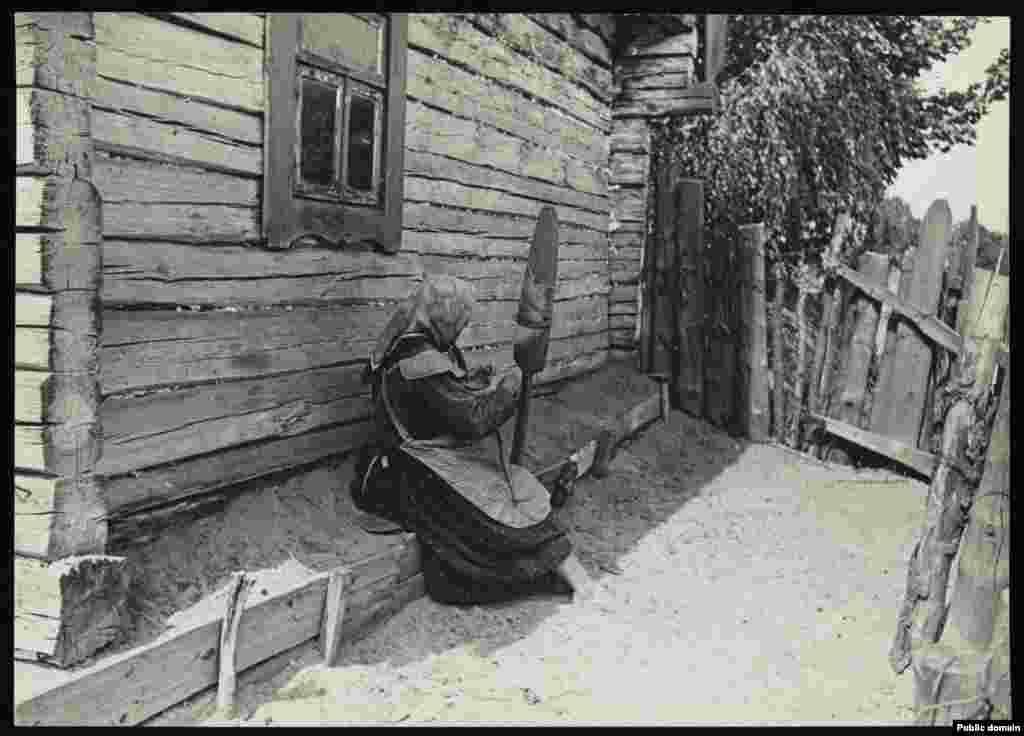 Женщина прядет во дворе своей хаты
