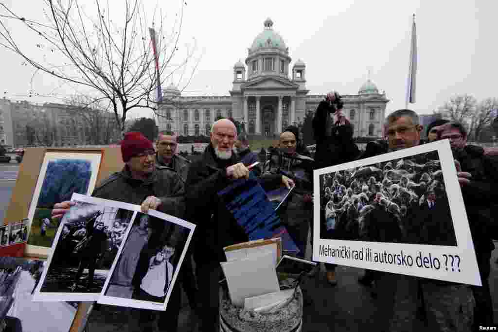 """Photojournalist Dragoljub Zamurovic (center) destroys his pictures during a protest in front of the parliament building in Belgrade. Photojournalists in Serbia appealed to lawmakers to reject a proposal by the ruling party to define their work as the result of a """"routine mechanical act"""" and therefore not worthy of copyright protection. The placard (right) reads, """"Mechanical work or a product of an author???"""" (Reuters/Marko Djurica)"""