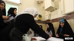 Women in Tehran cast ballots in the country's runoff election for parliament.