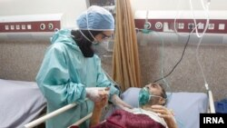A nurse attends to a coronavirus patient in Iran.