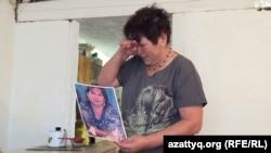 66-летняя Рауза Амиржанова с портретом дочери, умершей в больнице. Село Бурлин Западно-Казахстанской области, 14 июля 2015 года.