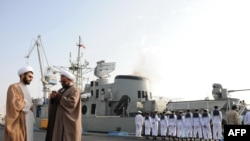 "Clerics stand in front of the ""Jamaran,"" Iran's first domestically built warship, during naval maneuvers in the Persian Gulf in February 2010."