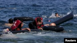 Refugees float as they hold a tube after a dinghy carrying Syrian and Afghan refugees deflated some 100 meters from the Greek island of Lesbos in September 13.