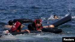 Refugees float as they hold a tube after a dinghy carrying Syrian and Afghan refugees deflated some 100m away before reaching the Greek island of Lesbos on September.