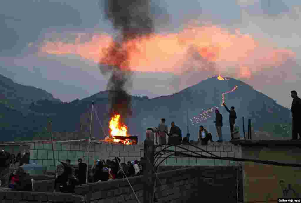 Locals gather around a bonfire as the torch procession winds up a hill above Aqrah, in northern Iraq, on March 20.