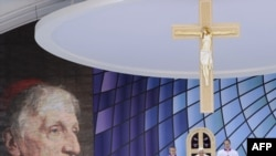 Pope Benedict XVI (center) presides over a Mass to beatify Cardinal John Henry Newman (left) in Birmingham today.