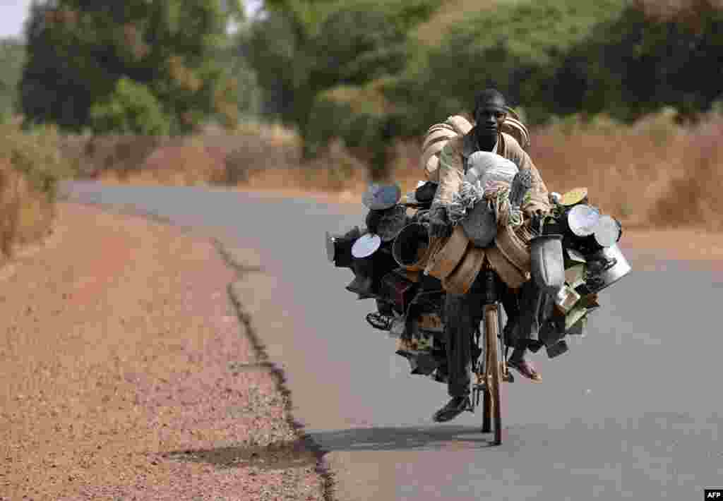 A man carries good to sell as he rides a bicyle en route to a market near Segou, north of Bamako, Mali. (AFP/Eric Feferberg)