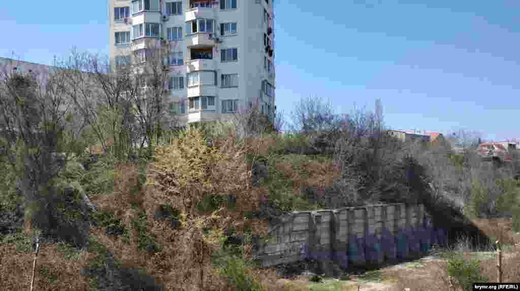 Над яром нависає дев'ятиповерхівка-свічка з вулиці Кокчетавської, схил тримає потужна підпірна стіна