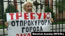 Жительница Алматы Ольга Панина на одиночном пикете у ограды городской прокуратуры, 28 августа 2015 года.