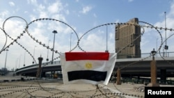 An Egyptian flag is hung on barbed wire by opposition supporters on the front line near Tahrir Square in Cairo
