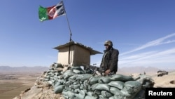 An Afghan National Army (ANA) soldier keeps watch at a check post in Logar province.