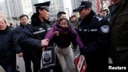 Қытай полицейлері сотта ісі қаралып жатқан Сюй Чжиюнге қолдау білдіріп келген адамды ұстады. Пекин, Қытай, 22 қаңтар 2014 жыл.