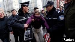 Китайские полицейские задерживают женщину, которая вышла на акцию в поддержку правозащитника Сюй Чжиюна.