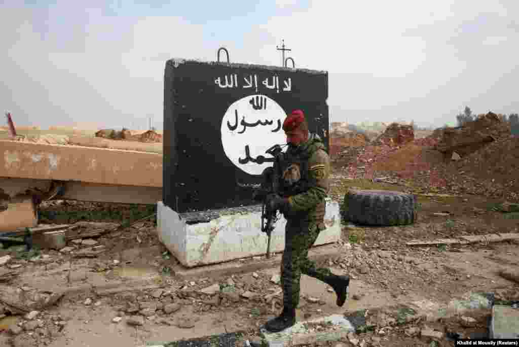 An Iraqi soldier walks next to a wall painted with the signature black flag used by IS militants in northern Iraq and elsewhere. The Arabic texts in the white banner at the top of the flag and inside the white circle contains the two-part Shahada creed associated with Sunni Islam.