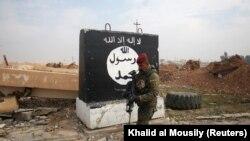 """""""Ислам мемлекеті"""" ұйымының туы салынған қабырғаның жанында кетіп бара жатқан Ирак сарбазы (Көрнекі сурет)."""