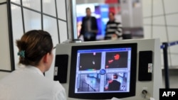 Macedonia - A health worker scans passengers with a thermal imaging camera upon their arrival at the Alexander the Great airport near Macedonia's capital Skopje on October 10, 2014