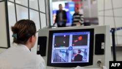Медицинский работник наблюдает за прибывающими в аэропорт пассажирами через тепловизор. Скопье, 10 октября 2014 года.