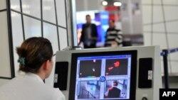 Медицинский работник наблюдает за прибывающими в аэропорт пассажирами через тепловизор.