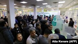 "Iranians wait to get medication and masks at the state-run ""13 Aban"" pharmacy in Tehran, February 19, 2020"
