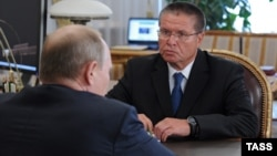 Russian President Vladimir Putin (foreground) speaks with Economy Minister Aleksei Ulyukayev. (file photo)
