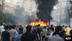 Supporters of Iran's presidential candidate Mir Hossein Mousavi standing by a burning vehicle during protests in Tehran, 19Jun2009