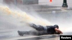 Струя водомета сбивает с ног демонстранта в Анкаре. 16 июня 2013 г.