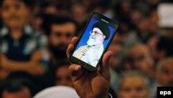 Një Iranian mban në duar një telefon, ku shfaqet fotografia e liderit suprem të Iranit, Ayatollah Ali Khamenei