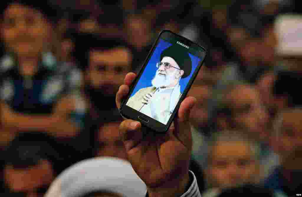 An Iranian man holds his mobile phone showing a picture of Iranian supreme leader Ayatollah Ali Khamenei as he attends ceremonies to mark the 26th anniversary of the death of Ayatollah Ruhollah Khomeini in southern Tehran on June 3. (epa/Abedin Taherkenareh)