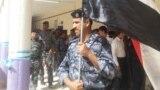 رجل أمن عراقي يرفع علم بلاده أثناء عملية التصويت الخاص في الإنتخابات البرلمانية
