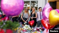 People look upon the flowers, messages, and tokens left in tribute to the victims of the attack on Manchester Arena.