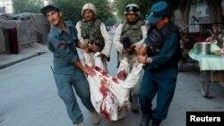 Қауіпсіздік қызметкерлері жарылыстан қаза тапқан адамды әкетіп барады. Ауғанстан. Көрнекі сурет.