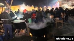Люди в масках готують гарячий напій у великому казані. Київ, 10 грудня 2013 року