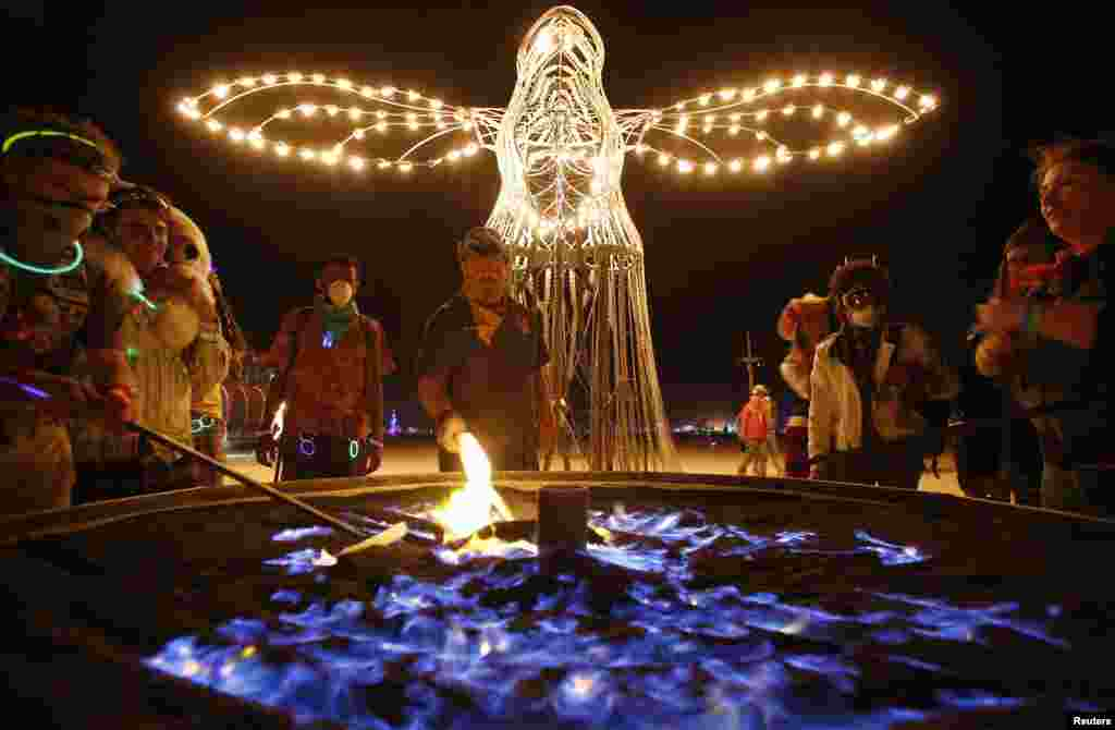 "Christian Jacobsen (center) stands by the ""Guardian of Dawn"" art installation during the Burning Man 2013 arts and music festival in Nevada's Black Rock Desert."