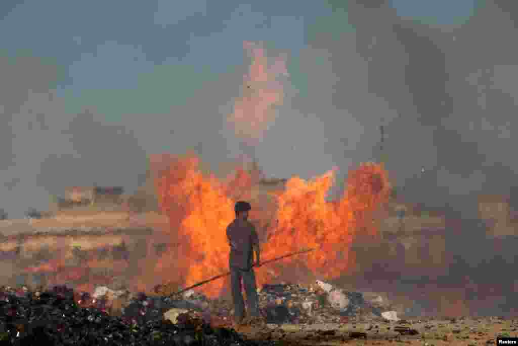 A Pakistani customs employee stands amid burning piles of confiscated contraband and narcotics destroyed during a campaign marking International Customs Day in Karachi on January 26. (Reuters/Akhtar Soomro)