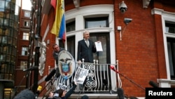 WikiLeaks founder Julian Assange holds a copy of a UN ruling as he makes a speech from the balcony of the Ecuadorian Embassy in central London in February.