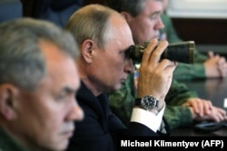 Russian President Vladimir Putin (center) and Defense Minister Sergei Shoigu (left) observe the Zapad-2017 exercises near Leningrad last year.