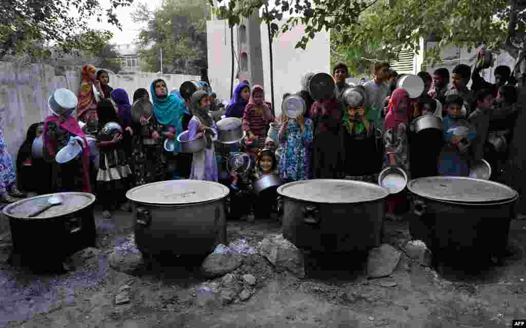 Afghan children hold dishes as they wait to receive food donated by a private charity during the holy month of Ramadan in Jalalabad on June 30. (AFP/Noorullah Shirzada)