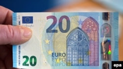 Germany --An employee of the German Federal Bank (Bundesbank) holds up a new 20 euro note in Duesseldorf, 04 November 2015.