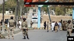 FILE: Paramilitary soldiers inspect the site of an attack in Balochistan.