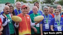Turkmen President Gurbanguly Berdymukhamedov (second left) takes part in the country's National Melon Day celebrations surrounded by officials and participants involved in the upcoming 2017 Asian Indoor and Martial Arts Games, in Ashgabat on August 18.