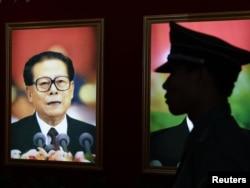 Полицей Цзян Цзэминьнің суреті алдынан өтіп бара жатыр. Бейжің, 7 шілде 2011 жыл.