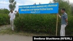 Жерлерінен айыруға қарсы тұрғындар конституциядан цитата жазылған баннер ұстап тұр. Астана, 28 маусым 2014 жыл. (Көрнекі сурет)