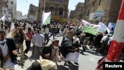 Yemeni antigovernment protesters flee as gunfire erupts during a demonstration in Sanaa on October 16.