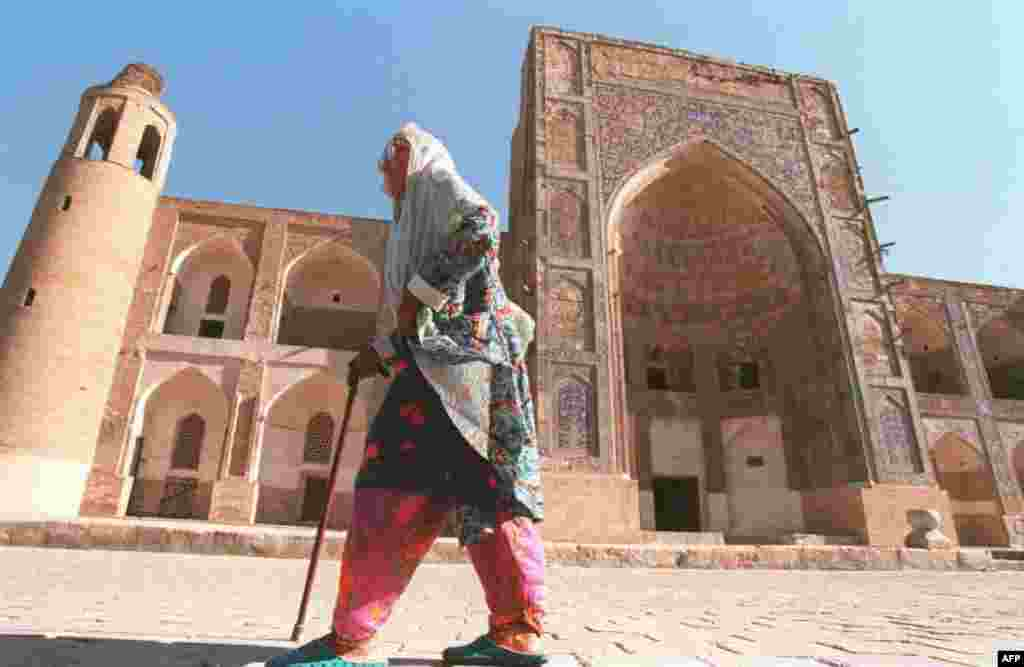 A woman walks past the Uluh-Beg Madrasah, a Koranic school in Bukhara.