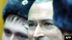 Mikhail Khodorkovsky stands between police officers at a courtroom in Moscow on December 27.
