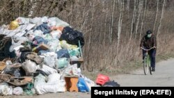 An elderly man wearing a respirator rides a bicycle past garbage bags to the grocery store during a lockdown, in Ramenskoye, outside Moscow, on April 9.