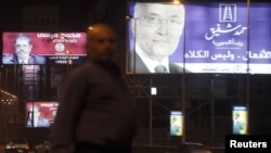 An Egyptian man in Cairo walks past campaign billboards for presidential candidates Ahmed Shafiq (right) and Muhammad Mursi (left) in late May.