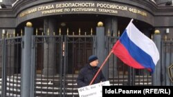 """Dmitry Berdnikov, leader of the movement Against Corruption and Lawlessness, stands in front of the FSB holding a poster saying: """"Where are you, FSB? Take measures to return money to clients of Tatfondbank and Intekhbank!"""""""