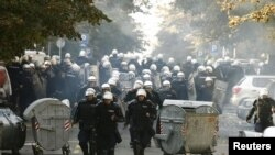 Riot police run down a street during clashes in Belgrade with antigay protesters on October 10.