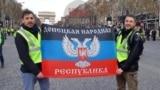 Флаг группировки «ДНР» во время протестов в столице Франции. Его держат: Фабрис Сорлин (слева) и Ксавье Моро
